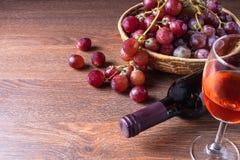 En flaska av rött vin och ett exponeringsglas av rött vin med röda druvor in royaltyfri fotografi