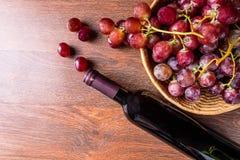 En flaska av rött vin och ett exponeringsglas av rött vin med röda druvor in royaltyfri bild