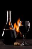 En flaska av rött vin och ett exponeringsglas som är främst av en spis Royaltyfri Fotografi