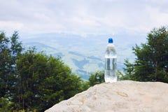 En flaska av rent dricksvatten i plast- flaska på berget arkivfoto