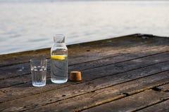 En flaska av vatten med citronen och ett exponeringsglas Bro som står på arkivbilder