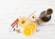 En flaska av vin, skivor av apelsinen, honung, kanel till funderat vin på vit arkivfoton