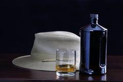 En flaska av whisky, ett exponeringsglas av whisky och en hatt på stången Arkivfoton
