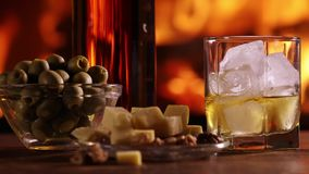 En flaska av whisky och ett exponeringsglas är på tabellen stock video
