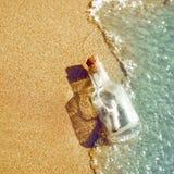 En flaska med ett meddelande kastas av en våg på en sandig strand Begrepp av hopp som flaskan svävar i bränninglinjen arkivfoton