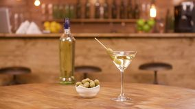 En flaska och ett exponeringsglas av martini med oliv på en trätabell lager videofilmer