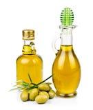 En flaska två av olivolja med oliv på plattan Royaltyfria Bilder