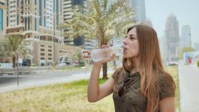 En flicka är dricksvatten från en flaska på en gata i staden av Dubai stock video