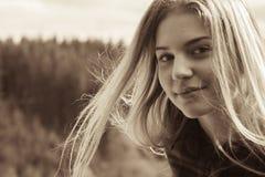 En flicka är roterande i vinden arkivfoto