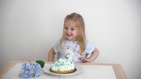 En flicka av 3 år gammal danandeönska som blåser stearinljus på den blåa kakan arkivfilmer