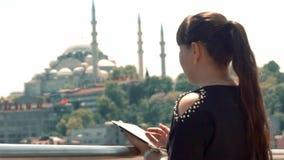 En flicka av asiatiska utseendemässiga ställningar nära en härlig sikt av staden och blickar på hennes minnestavla arkivfilmer