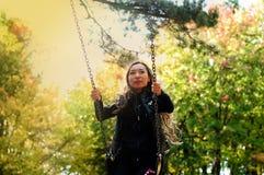 En flicka av det orientaliska utseendet åker skridskor på en gunga Arkivfoto