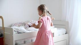 En flicka av 3 gamla år gör en säng i barnrummet lager videofilmer