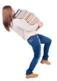 En flicka bär en tung hög av böcker tillbaka sikt Peopl för bakre sikt Arkivbilder