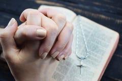 En flicka ber över den heliga bibeln Arkivfoto