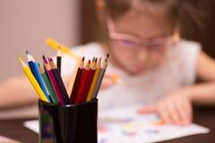 En flicka drar med kulöra blyertspennor arkivfoton