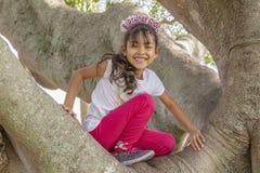 En flicka för lycklig födelsedag ler uppifrån av trädet royaltyfria bilder