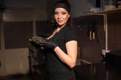 En flicka förbereder hamburgaren i köket av restaurangen arkivbild