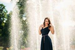 En flicka går runt om staden, nära en stor springbrunn Arkivfoton