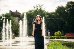 En flicka går runt om staden, nära en stor springbrunn Arkivfoto