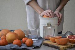 En flicka gör ny grapefruktfruktsaft arkivbilder