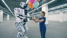 En flicka ger upp kulöra ballonger till en robot, slut arkivfilmer