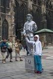 En flicka har hennes fotografi att tas med en målad statygataaktör i silver i Wien i Österrike Arkivbild
