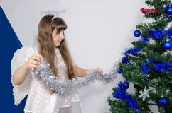 En flicka i en ängeldräkt dekorerar julgranen royaltyfri foto