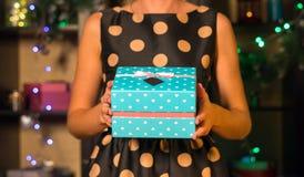 En flicka i en aftonklänning ger en gåva för nytt år Royaltyfri Fotografi