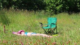 En flicka i en baddräkt solbadar på gräsmattan Bredvid henne i en picknickstol lager videofilmer