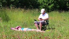 En flicka i en baddräkt solbadar på gräsmattan Bredvid henne i en picknickstol sitter spelar en man och i smartphonen lager videofilmer