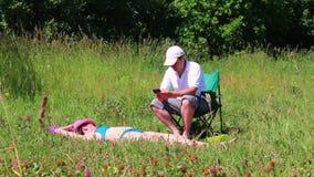 En flicka i en baddräkt solbadar på gräsmattan Bredvid henne i en picknickstol sitter spelar en man och i smartphonen arkivfilmer