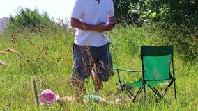 En flicka i en baddräkt solbadar på gräsmattan Bredvid henne i en picknickstol sitter spelar en man och i smartphonen Därefter få stock video