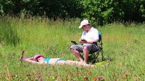 En flicka i en baddräkt solbadar på gräsmattan Bredvid henne i en picknickstol sitter spelar en man och i smartphonen Ta en bott lager videofilmer