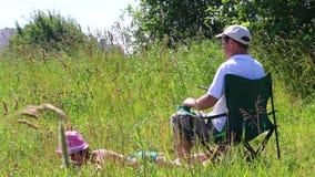 En flicka i en baddräkt solbadar på gräsmattan Bredvid henne i en picknickstol sitter spelar en man och i smartphonen Ta en bott arkivfilmer
