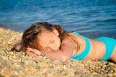 En flicka i en blå baddräkt arkivfoto