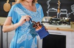 En flicka i en blå klänning maler kaffe Flicka med en kaffekvarn royaltyfri bild