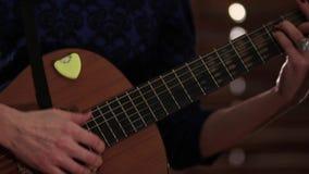 En flicka i en blå klänning spelar en akustisk gitarr Händer på raderna av ett musikinstrument Närbild stock video