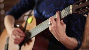 En flicka i en blå klänning spelar en akustisk gitarr Närbild Händer på raderna av ett musikinstrument Defocus på slutnollan arkivfilmer