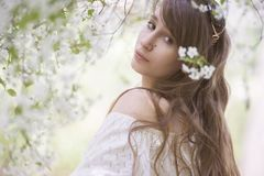 En flicka i en blommande trädgård royaltyfri fotografi
