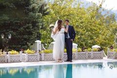 En flicka i en bröllopljusklänning rymmer en bukett av blommor och trycker på försiktigt framsidan av mannen, iklätt a royaltyfria bilder