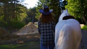 En flicka i en cowboyhatt går med en häst på en lantgård lager videofilmer