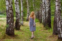En flicka i en affärsklänning går till och med trädgården Arkivbilder