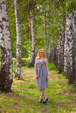 En flicka i en affärsklänning går till och med trädgården Royaltyfria Foton