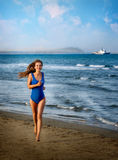 En flicka i en baddräkt kör längs stranden Royaltyfri Bild