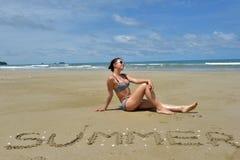 En flicka i en baddräkt sitter på en öde sandig strand Fotografering för Bildbyråer