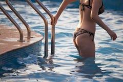 En flicka i en baddräkt stiger ned in i pölen Royaltyfri Foto