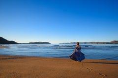 En flicka i en klänning står vid havet royaltyfria bilder