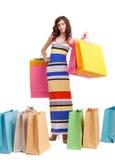 En flicka i en lång klänningfärg med shopping bags Fotografering för Bildbyråer