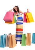En flicka i en lång klänningfärg med shopping bags Arkivbild
